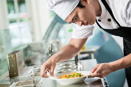 Gourmet chef plating up a dish of food in an Asian restaurant carefully wiping the sides of the plate for spillage