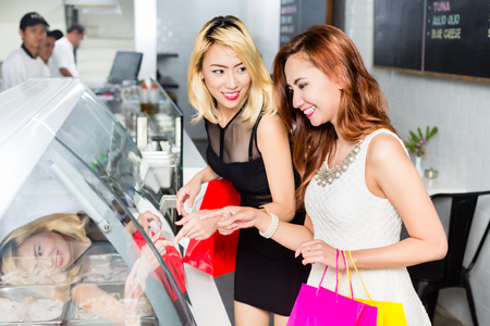 Couple of attractive stylish Asian ladies choosing food in a restaurant standing at a glass counter with their shopping bags chatting and pointing Stock Photo