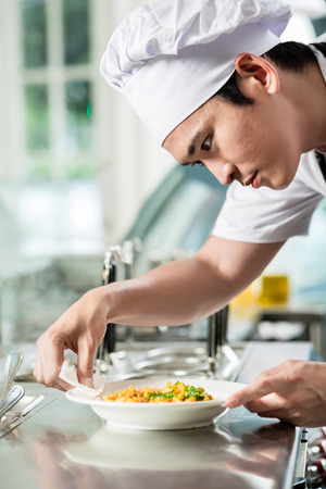 Handsome young Asian chef plating up food in a commercial kitchen carefully wiping around the dish before serving the customer