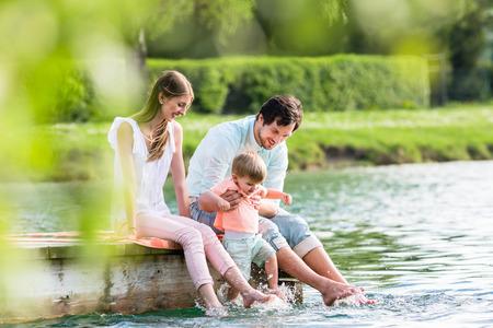 Szczęśliwa rodzina siedzi na molo nad jeziorem lub stawem, pozwalając stopom zwisać w wodzie