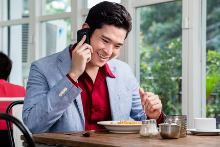 Handsome stylish formal young businessman talking on a mobile phone as he sits at a restaurant table enjoying lunch