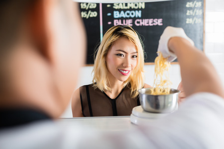 Asian woman watching intently as grated cheese is placed on a scale for weighing in a restaurant or deli in an over the shoulder view from behind the shop assistant