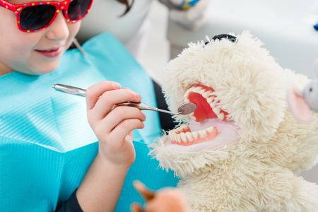 Child at dentist office looking after teeth of pet toy
