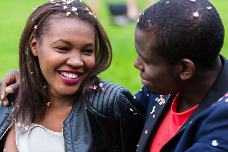 Black couple, woman and man, smiling at each other, sitting on lawn, confetti on them from a street party Stock Photo