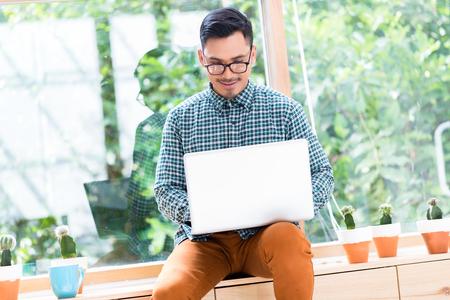 Entspannter junger asiatischer Angestellter, der an Laptop beim Sitzen auf einem hölzernen Fach im Büro arbeitet Standard-Bild