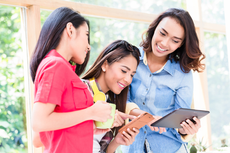 Three young and beautiful Asian women having fun while looking at a tablet PC during break at work