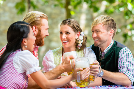 In beer garden - friends in Bavarian clothes drinking beer in Bavaria, Munich, Germany Stock Photo - 90309972