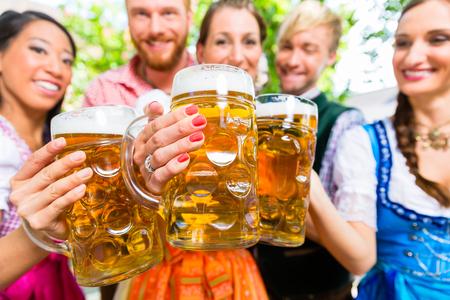 Friends, two men, three women, standing in beer garden with beer glasses Stock Photo
