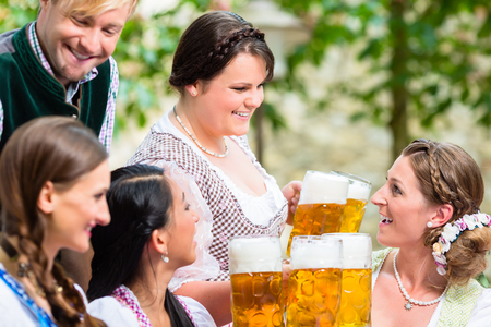Waitress in beer garden serving drinks to three women and man