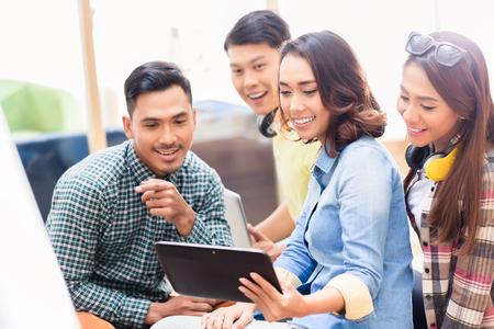 Équipe créative de quatre jeunes employés regardant une présentation professionnelle surprenante sur une tablette PC au bureau