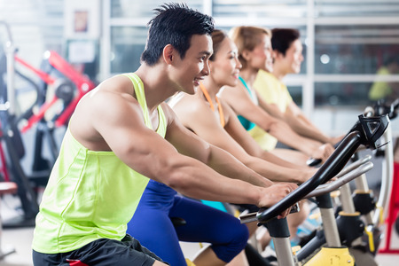 Group of young Asian athletes side by side during spinning class workout Stockfoto