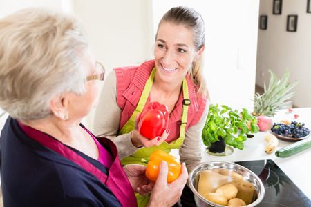 Mother in law explaining correct use of bell pepper in kitchen to her daughter in law once again Stockfoto