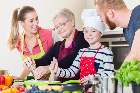 Family cooking in multigenerational household with son, mother, father and grandfather Stock Photo