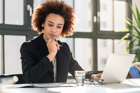 Portrait of African American female expert analyzing printed business report while sitting at desk in the office