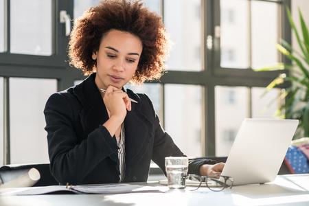 Ritratto dell'esperto femminile afroamericano che analizza relazione di attività stampata mentre sedendosi allo scrittorio nell'ufficio Archivio Fotografico - 90443453