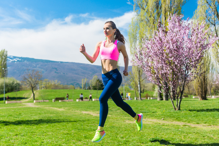 Woman running fast for sport on sunny day Stock Photo