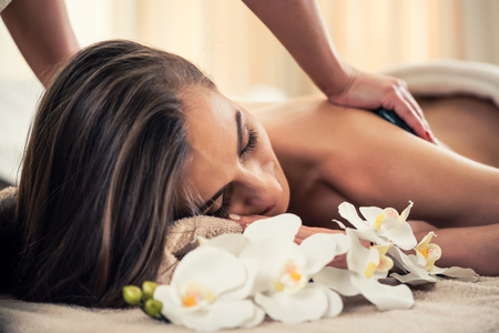 Young woman enjoying the therapeutic effects of a traditional hot stone massage at luxury spa and wellness center