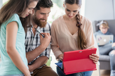 Reliable digital nomads cooperating for helping their co-worker during remote work on a tablet PC in a modern collaborative space Stock Photo