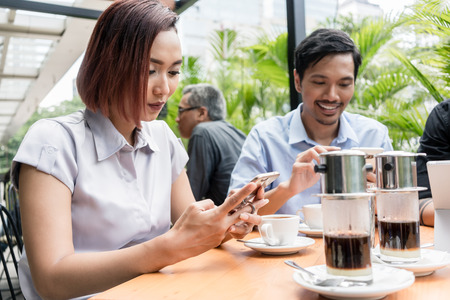 Three young Asian friends smiling while using electronic devices connected to the wireless internet network of a modern coffee shop Stock Photo
