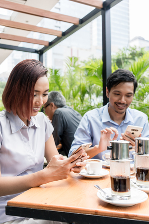 Three young Asian friends smiling while using electronic devices connected to the wireless internet network of a modern coffee shop Stock fotó