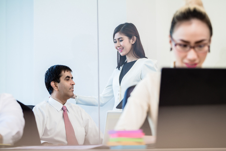 Office co-workers talking gossip behind back of Asian business woman working at laptop Stock Photo