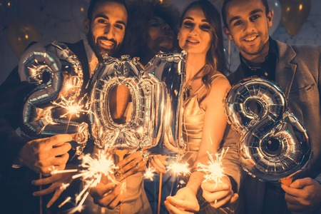 Men and women celebrating the new year 2018 with sparklers and wine