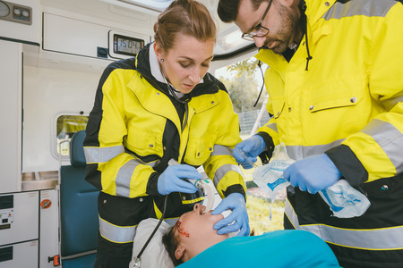 Emergency medics performing reanimation on clinically dead woman in ambulance 스톡 콘텐츠