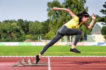 Female sprinter leaving starting blocks on running track in stadium
