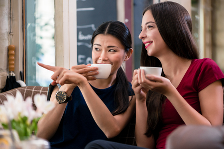Chatty Asian young woman pointing while sitting with her best friend in a coffee shop