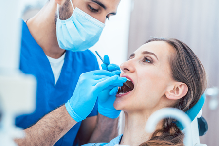 Side view of a young woman during painless teeth cleaning done in a modern medical center