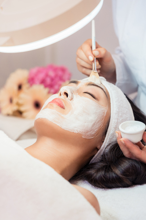 Close-up of the face of a young woman relaxing under the gentle touch of the specialist applying on her cheeks, white facial mask with rejuvenating effects