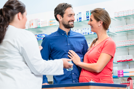 Woman and man in pharmacy shopping talking to sales lady