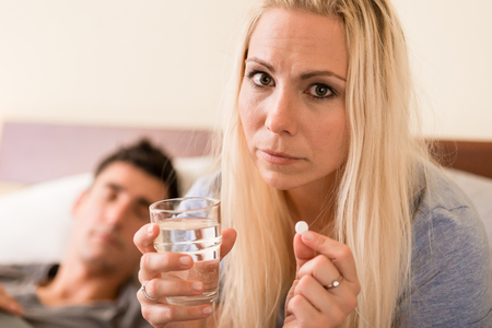 Young worried woman sitting in bed next to her partner while taking a pill before sleep at night Stock Photo
