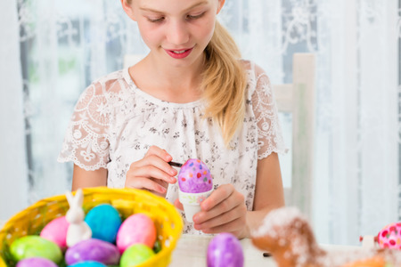 Girl is coloring Easter eggs by painting on them Stock Photo