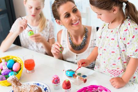 Family having fun coloring Easter eggs