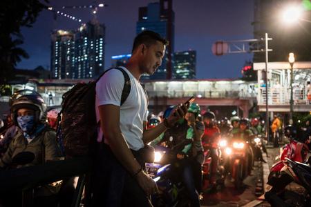 자카르타에서 밤에 스쿠터에 사람들과 붐비는 거리를 걷는 동안 휴대 전화를 사용하여 젊은 남성 관광객 스톡 콘텐츠