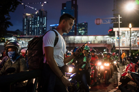 Young male tourist using the mobile phone while walking on a crowded street with people on scooters in Jakarta at night Banque d'images