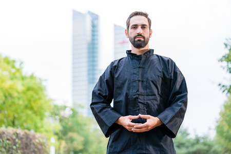 Man meditating doing martial arts in city