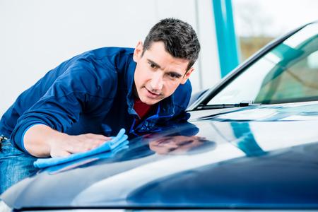 清潔な青い車の表面を乾燥し、磨く吸収性の柔らかいタオルを使用する若い男性