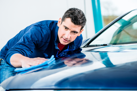 Young man using an absorbent soft towel for drying and polishing the surface of a clean blue car Archivio Fotografico