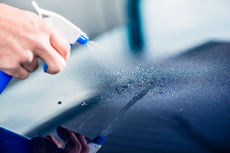 Close-up of hand spraying cleaning substance on the surface of a blue car at auto wash Foto de archivo