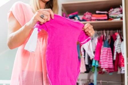 Soon-to-be mom shows girls clothes with anticipation in baby room Stockfoto