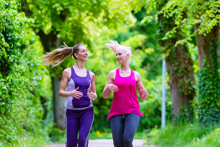 Two women running next to each other in a park with green trees Stock Photo