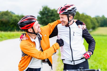 Bicyclists doing fitness sport embrace each other in finish, celebrate victory