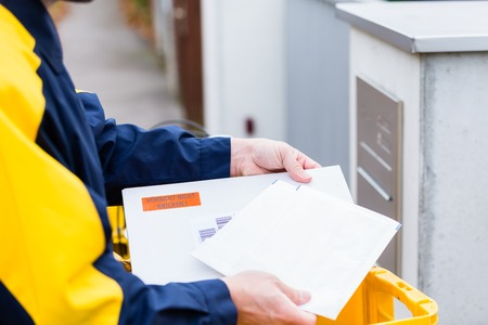 Postman delivering letters to mailbox of a recipient