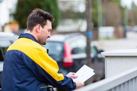 Postman delivering letters to the mailbox of recipient Stock Photo