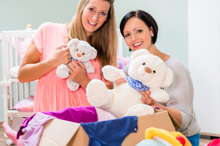 Expectant mother and her friend preparing nursery for baby