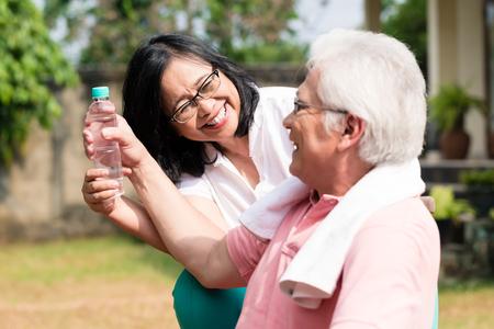 Zorgvuldige hogere vrouw die een fles water geeft aan haar partner in openlucht in een de zomerdag