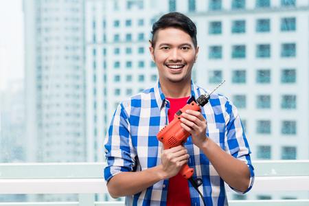 Young indonesian man with power drill, ready for home improvement Stock Photo