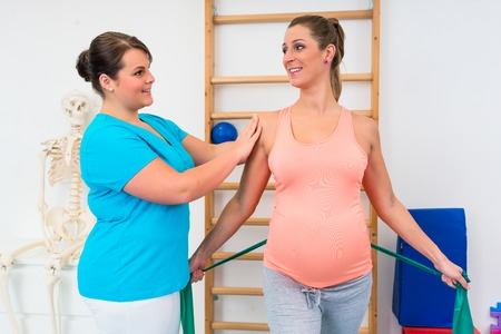Pregnant woman working out with physical therapist and resistance band